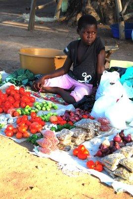 Girl grumpily sells vegetables at roadside