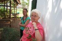 Aunt Margaret chews on a neem twig to clean her teeth. Lizzie looks on unimpressed