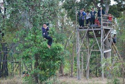 M6 student, Komsan, riding the zipline jump at scout camp