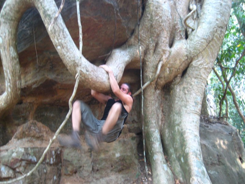 Ken getting ready to hang from a tree root at Kbal Spean
