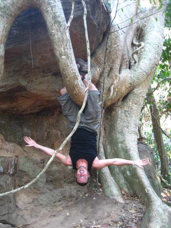 Ken hanging from a tree root at Kbal Spean