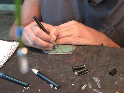 An artist engraving our names on a single piece of rice at the Copacabana night markets