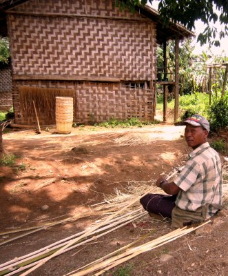 Man weaving bamboo baskets at the village while the women work the fields