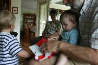 Benny opening a present with Opa and Miles assisting