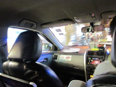View from the backseat of a taxi. In Macau, steering wheels are on the right and cars drive on the left side of the road.