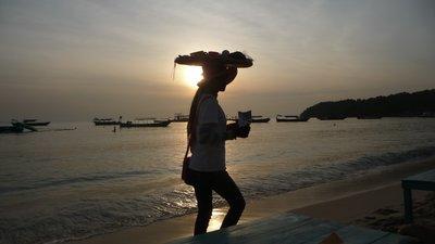 Lady carries stuff on head Sihanoukville beach
