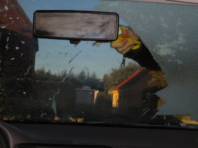 Aaron scraping frost from car windscreen