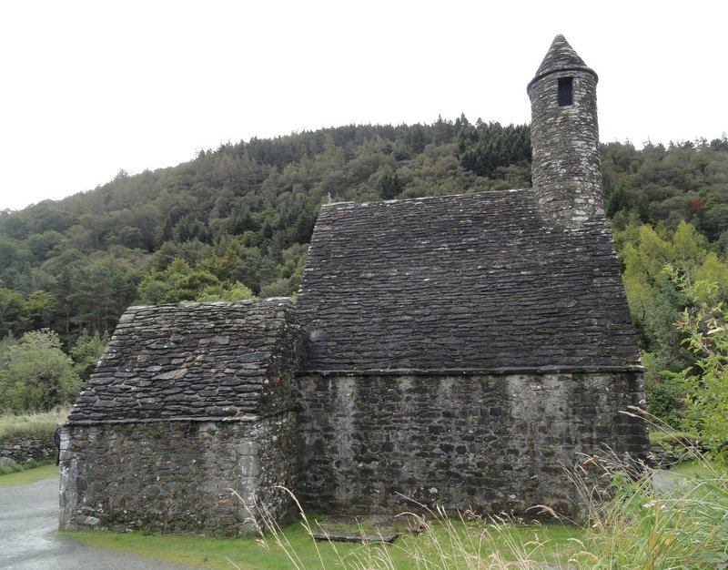 St Kevin's Church with a steeply pitched roof and round tower belfry (12th C)