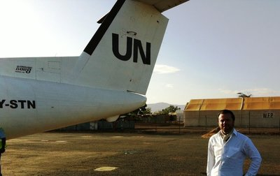 Boarding a UN aircraft. WFP storage tents in the backgound.
