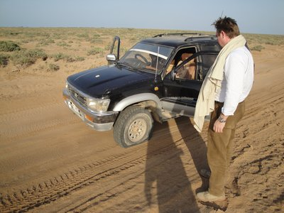 Harald watching the punctured tyre - in desert, just before sunset - no tools