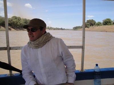 Harald crossing the Omo River, unfinished bridge behind