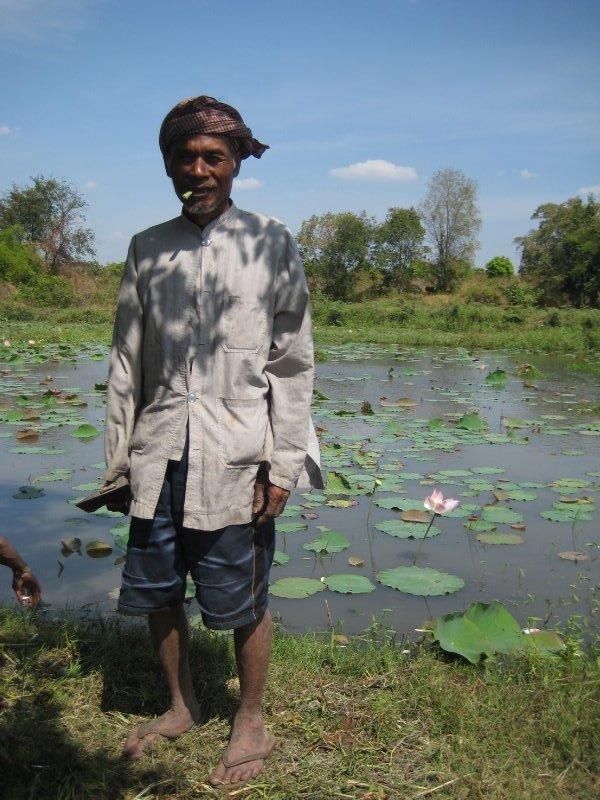 kheang's father smoking local tobacco, lotus pond