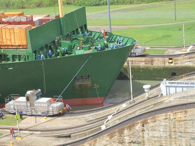 Ships are tied to trollies that travel along a track the length of the locks.  They ensure that the ship stays aligned while in the lock system and while passing through the gates.