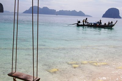 Passing fishing boats complete the picture-perfect sight in Koh Ngai