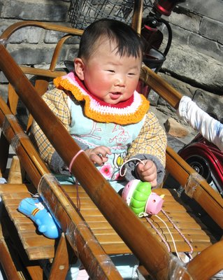 Chubby Chinese Baby in his baby cart in Hutong Town