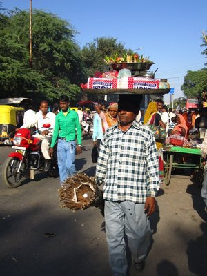 This man is talented. Balancing his food tray on his head, while carrying the stand.