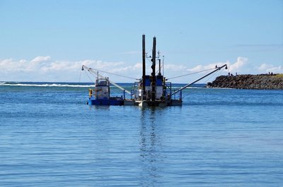 Dredge moored in position in the Tallebudgers Creek, ready to pump sand to Burleigh Beach..
