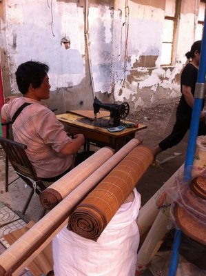 Man sewing mats to size across from hotel