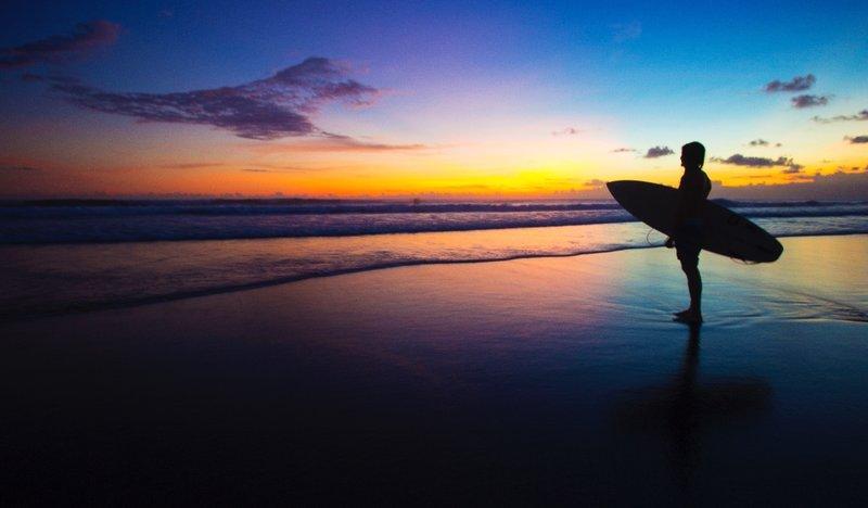 Surfer at sunset on Seminyak beach