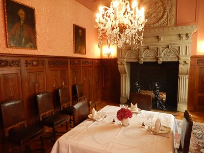 The dining room was renovated in 1909 by combining two rooms; a neo-Renaissance fireplace and family portraits adorn the room