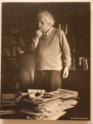 Einstein ponders a problem in his paper-filled study in Princeton, NJ; Steichen only had 5 of his own photos included in the exhibition
