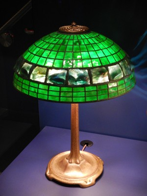 The Four Feet Base (ca. 1906-10) sold for $25 in 1906 while the Plain Squares, Turtleback Band Shade (ca. 1900-06) sold for $50; the geometric shapes required less labor so were less expensive than other Tiffany shades