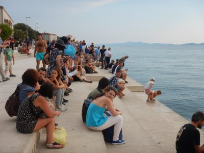These tourists are sitting on the sea organ, the most famous sight in Zadar; tide, waves and wind combine to push air through 35 vertically installed tubes of different lengths, diameters and slants
