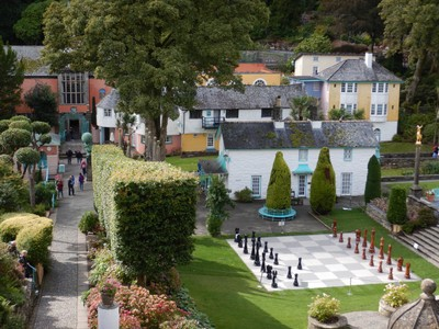 Portmeirion is not a real town but a private development which charges visitors $15 if you want to explore the village; I suspect the village would be packed in the summer