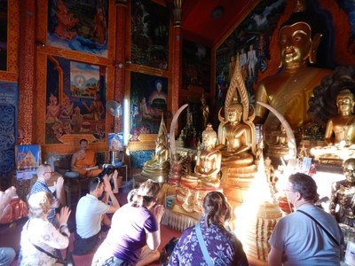 Our tour group going through a Buddhist prayer with the monk at Wat Phra That Doi Suthep with the monk then giving the group his blessing; the temple is said to have been founded in 1383 when the first stupa was built