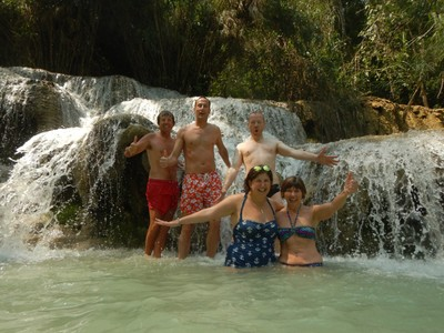 Five of us braved the cold water to truly experience the Tat Kuang Si Waterfalls; we may be smiling but small fish are biting at our feet