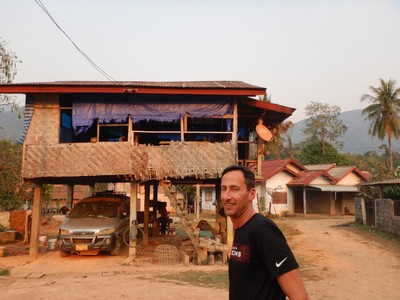 Jonathan in front of a typical rural Laos house where the bottom floor traditionally has housed livestock, chickens and other animals; the second level has all the living space with multi-generational families sharing being the norm