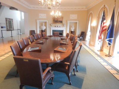 A replica of the Cabinet Room; the President's chair is a little higher and larger than the others with each cabinet secretary having a specific chair