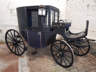 1890 carriage pulled by one horse with a coachman; it was built for the grandparents of Mrs. Linckets (the last governess)