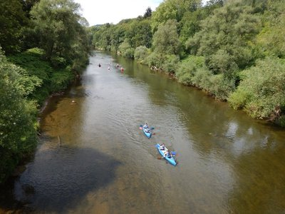 Kayakers trying to avoid hitting bottom on the shallow Sure River that separates Luxembourg (left) from Germany (right)