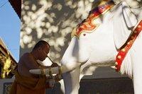 A Buddhist monk gives Doi Suthep's holy elephant a fresh lick of paint