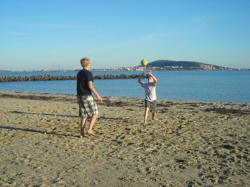Volleyball on the Mèze beach with a view of Sète in the background.