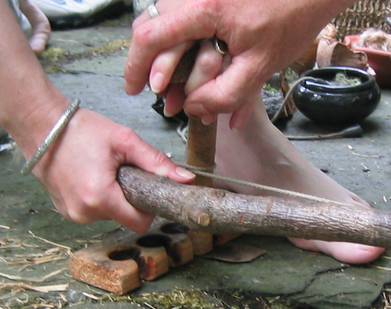 Close up of bow drill friction fire making