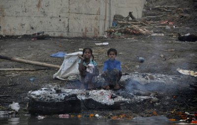 Street kids keep warm at a funeral pyre
