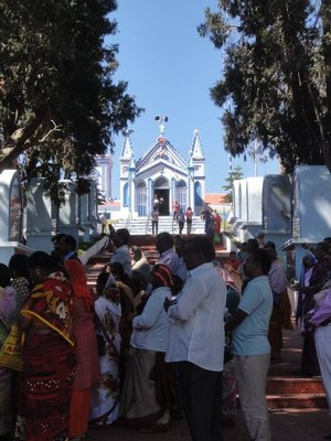 The church with mass going on and people doing the stations of the cross