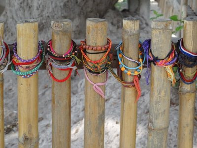 Friendship bracelets left in remembrance by a mass grave for women and children in the Killing Fields.