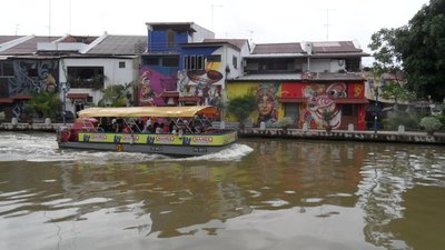 A tourist boat cruises past the murals on the riverbank