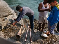 Devprayag_An off-duty Bengal Engineer from Roorkee cleaning the temple instruments in the river