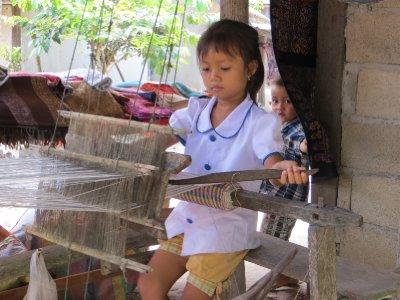 Little girl weaving scarfs