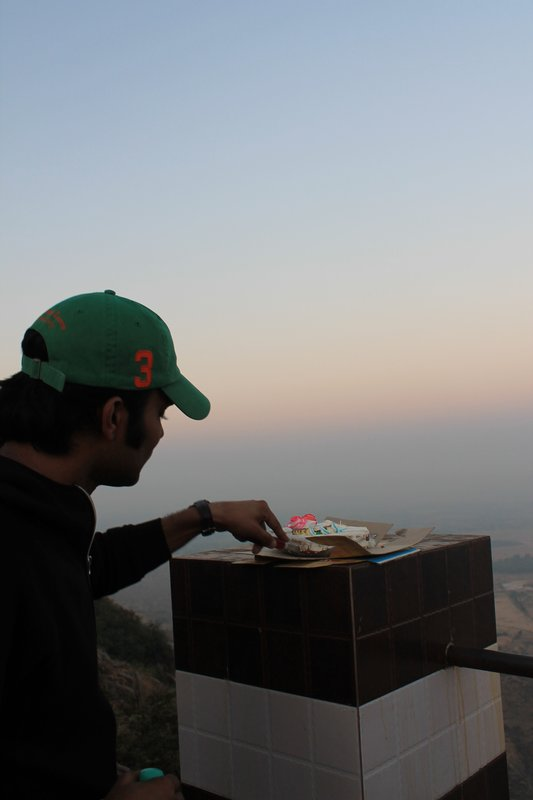 Raghu and his birthday cake on top of the mountain