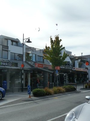 Skydivers coming into land high above Shotover Street (note the shop names - only in Queenstown!)