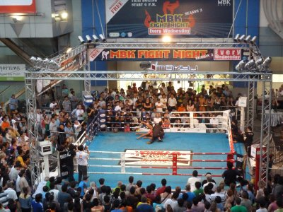 One of the boxers is floored during a Thai Boxing Bout