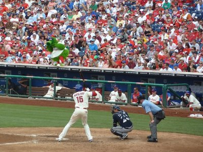Phillie Phanatic tries to 'hex' the opposing pitcher as John Mayberry prepares to hit the ball for Philadelphia
