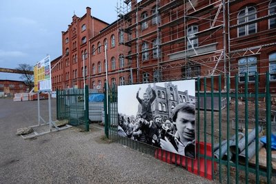 The photo, part of an outdoor exhibition at the shipyard, depicts Lech Walesa being carried by his peers in celebration in front of this very building