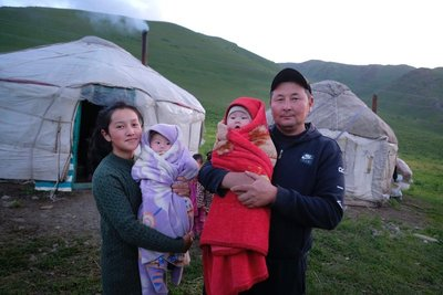 Proud parents at a yurt camp near Taldy Bulak