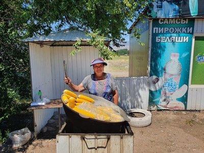A woman selling fresh steamed corn on the side of the road